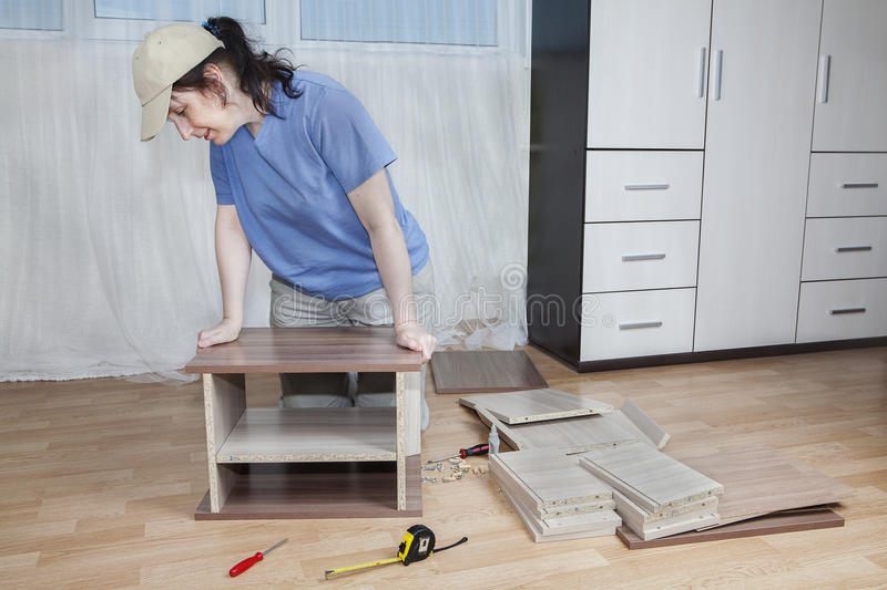 Assemble furniture, carpenter apply glue and clamp two boards to royalty free stock image
