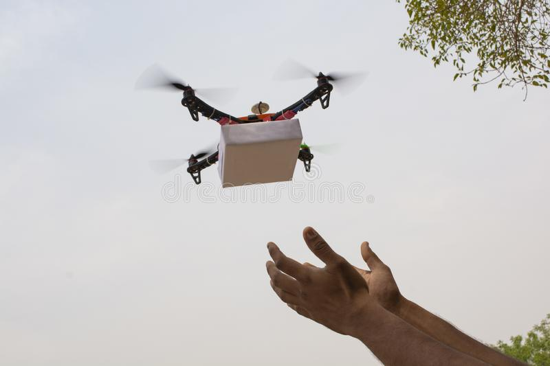 Assembled Drone quadcopter delivering a package and hands receiving the parcel. Assembled Drone quad-copter delivering a package and hands receiving the parcel stock images