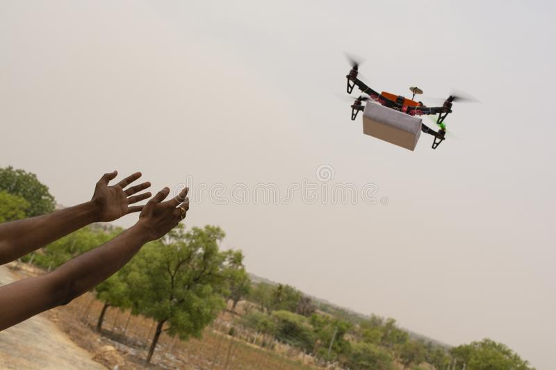 Assembled Drone quadcopter delivering a package and hands receiving the parcel. Assembled Drone quad-copter delivering a package and hands receiving the parcel royalty free stock images