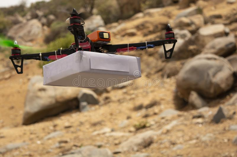 Assembled Drone quadcopter delivering a package with mountain as a background. Assembled Drone quad-copter delivering a package with mountain as a background royalty free stock image