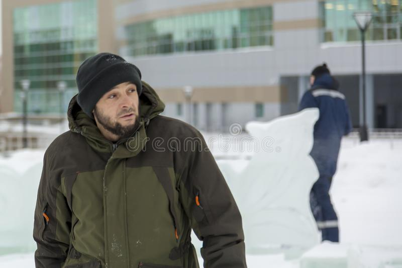 Assembler in overalls on the territory of the ice town stock images