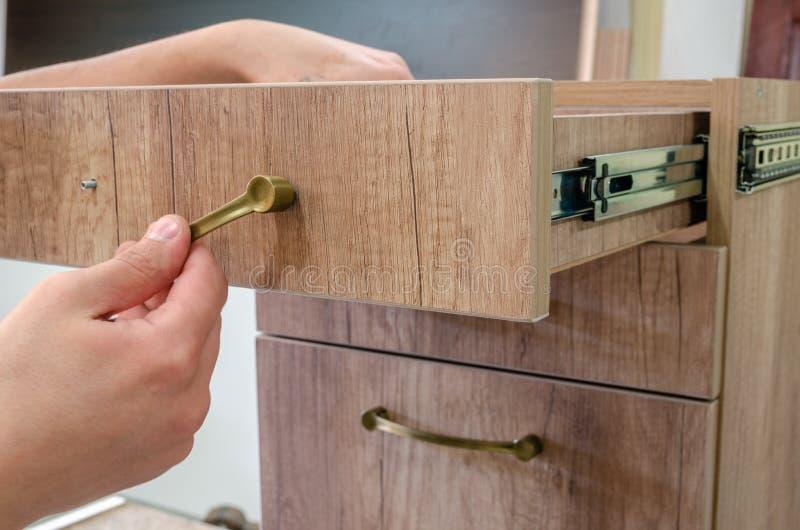 Assemblerend meubilair, die meubilair decoratieve handvatten installeren op de meubilairvoorgevel stock afbeeldingen
