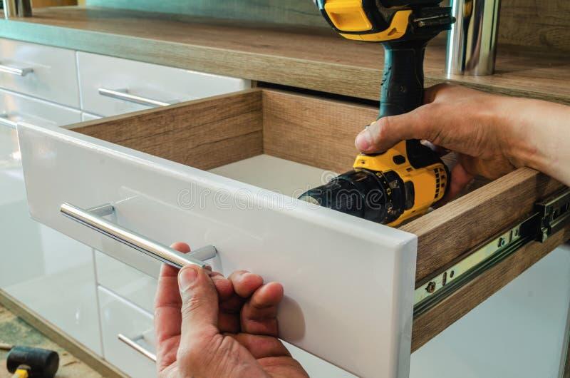 Assemblerend meubilair, die meubilair decoratieve handvatten installeren op de meubilairvoorgevel stock fotografie