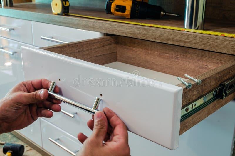 Assemblerend meubilair, die meubilair decoratieve handvatten installeren op de meubilairvoorgevel stock foto's