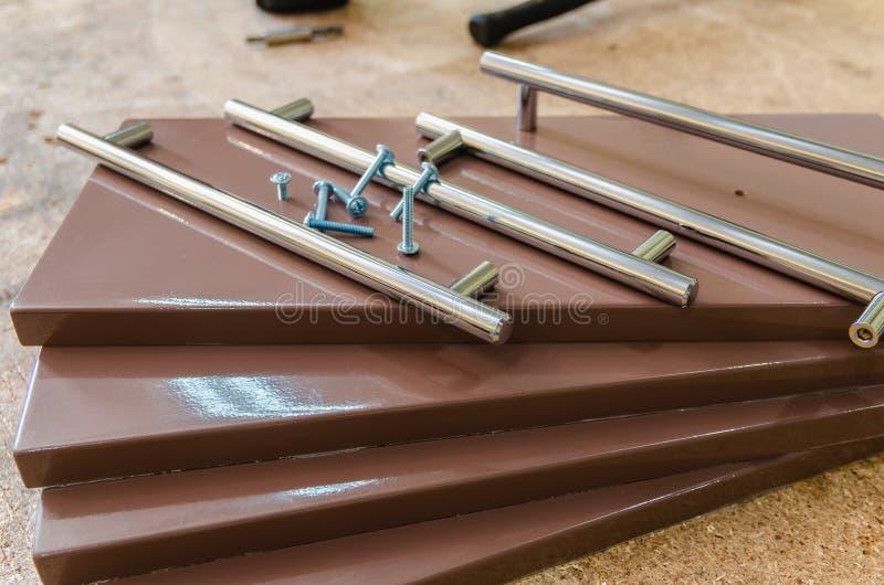 Assemblerend meubilair, die meubilair decoratieve handvatten installeren op de meubilairvoorgevel royalty-vrije stock afbeelding