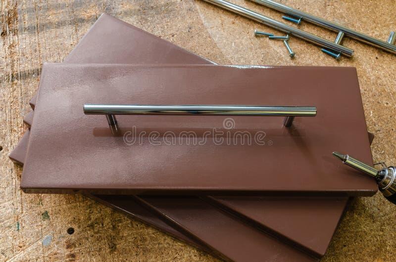 Assemblerend meubilair, die meubilair decoratieve handvatten installeren op de meubilairvoorgevel stock foto