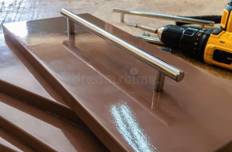 Assemblerend meubilair, die meubilair decoratieve handvatten installeren op de meubilairvoorgevel stock afbeelding