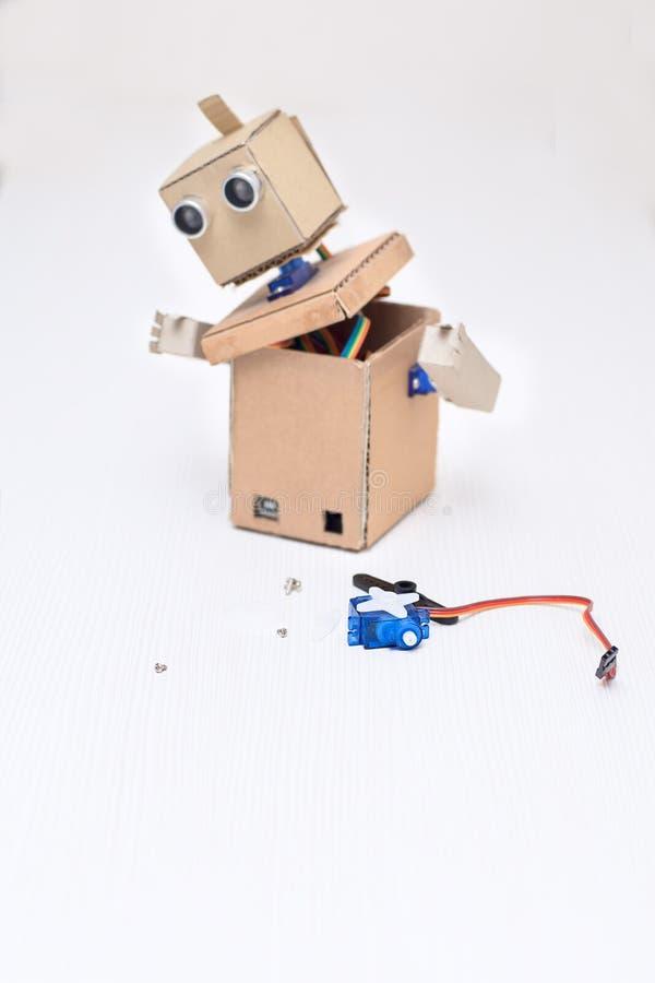 Assemblerende kartonrobot en de noodzakelijke details royalty-vrije stock afbeelding