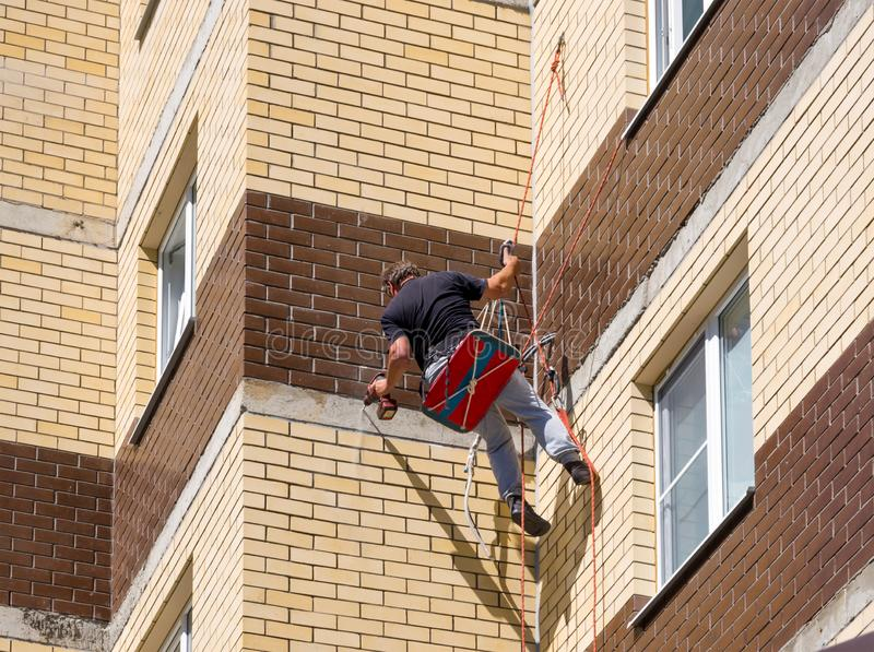 Assemblers drill a wall at home using climbing equipment stock image