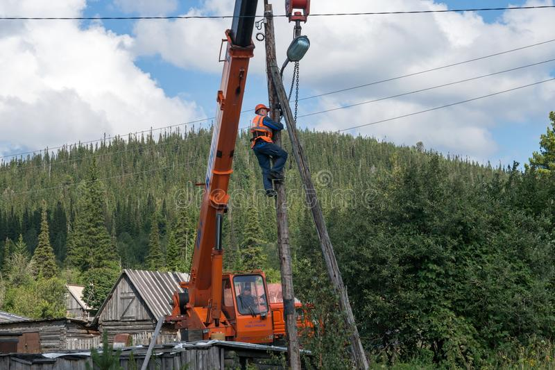 Assembling climbed a pole and tie him with chains to the crane boom for further disassembly. stock images
