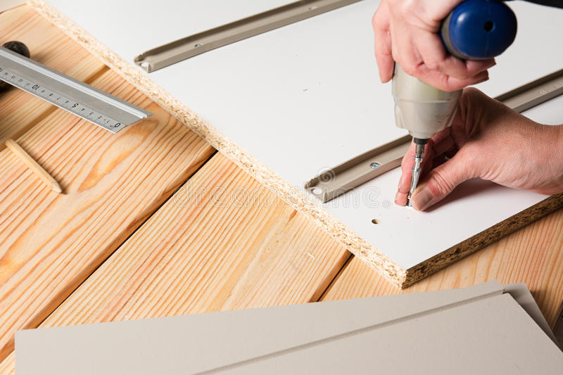 Assembling furniture from chipboard, using a cordless screwdriver stock photos