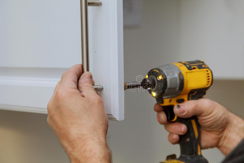 The worker installing handle the white cabinet with a screwdriver. Assembling of furniture closeup worker installing handle the white cabinet with a screwdriver royalty free stock photo