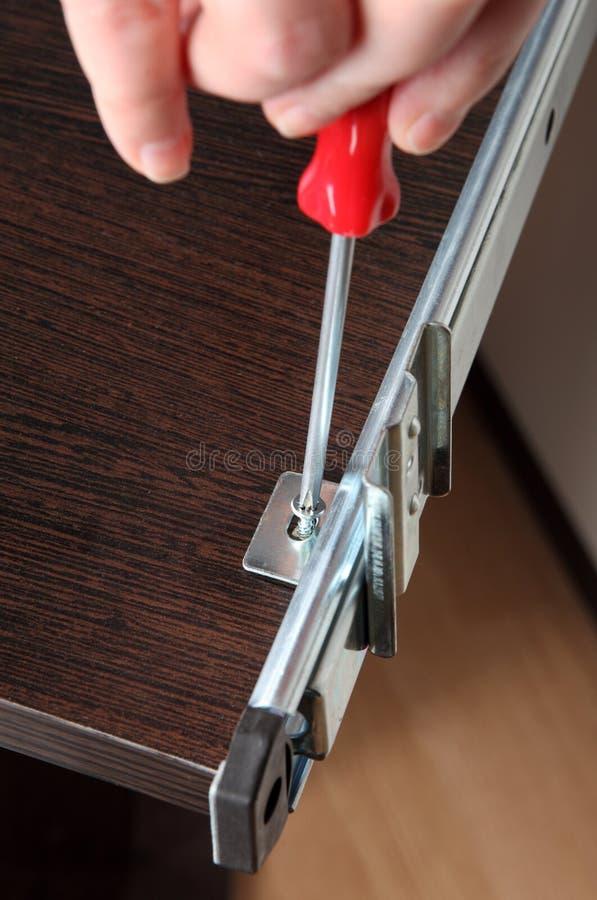 Assembling furniture, Installing drawer slide rear mounting bracket, screwing screw. stock photos
