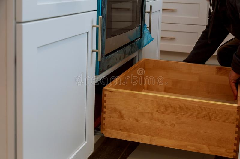 Assembling furniture white large drawers in new cabinet. Assembling furniture white large drawers of a kitchen with new cabinet, adjustment, assemble, woodworker royalty free stock images