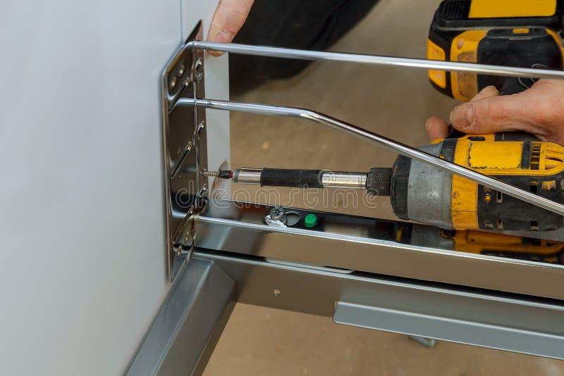 Assembling furniture white large trash can screws using a screwdriver. Assembling furniture white large drawers trash can screws using a screwdriver garbage bin royalty free stock image