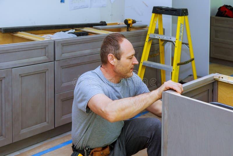 Assembling furniture white large trash can screws using a screwdriver. Assembling furniture white large drawers trash can screws using a screwdriver garbage bin royalty free stock photo