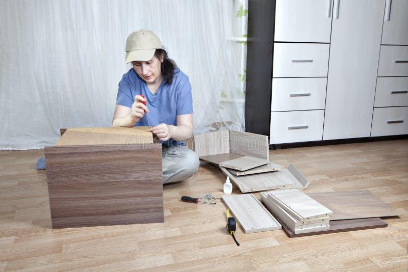 Assembling furniture, woman mounts nightstand screwing hardboard stock photography