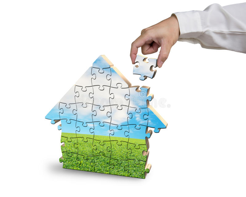 Assembling house shape puzzles in beautiful landscape royalty free stock photo