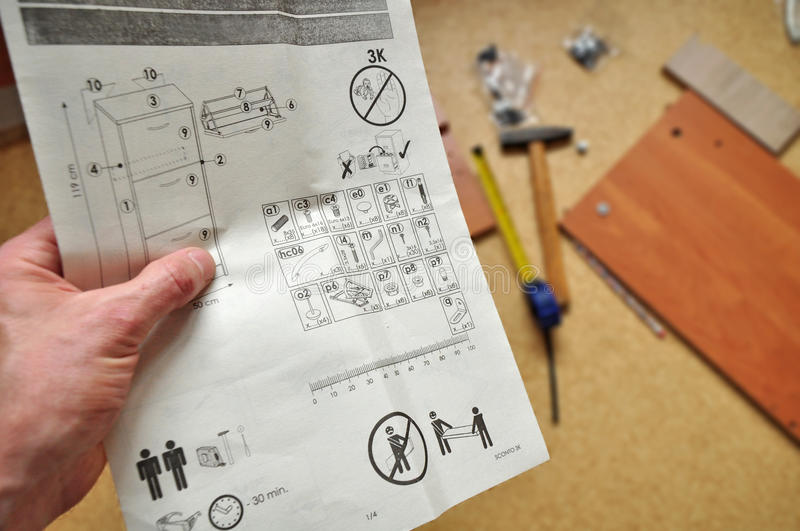 Assembly work home. Assembly. Man assembling furniture at home, reading work instructions royalty free stock photo