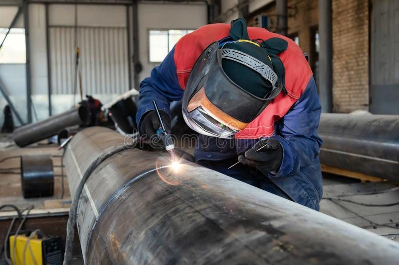 Welder, arc welding and weld seam close-up. Assembly of pipeline assemblies in the Assembly shop using argon-arc welding. Welder, arc welding and weld seam close royalty free stock image