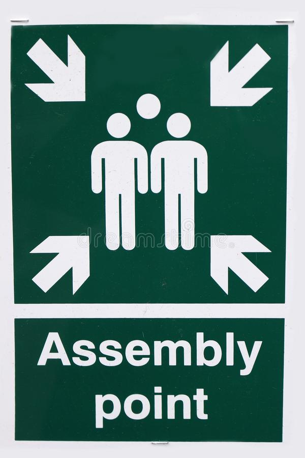 Assembly Point. Green and White Assembly Point Sign Showing People and Arrows stock image