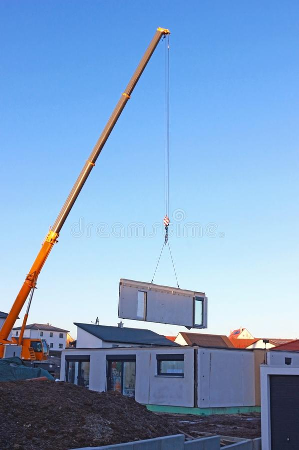 Assembly of a prefabricated house, crane lifting a wall component. With doors up in the air stock images