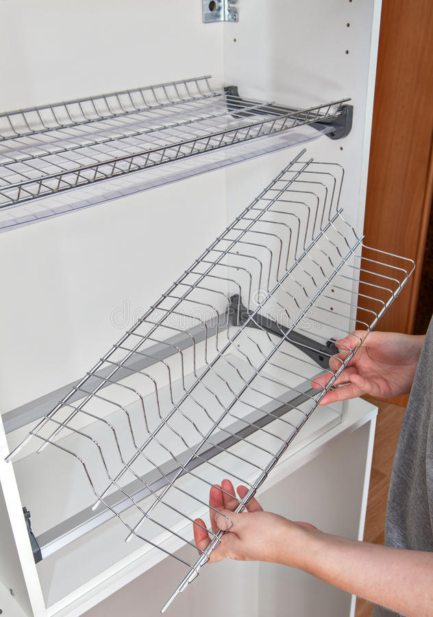 Assembly wire dish rack for drying dishes inside kitchen cabinet. Install wall mounted shelf under kitchen cabinet with inside dish rack with drip tray, close-up stock image