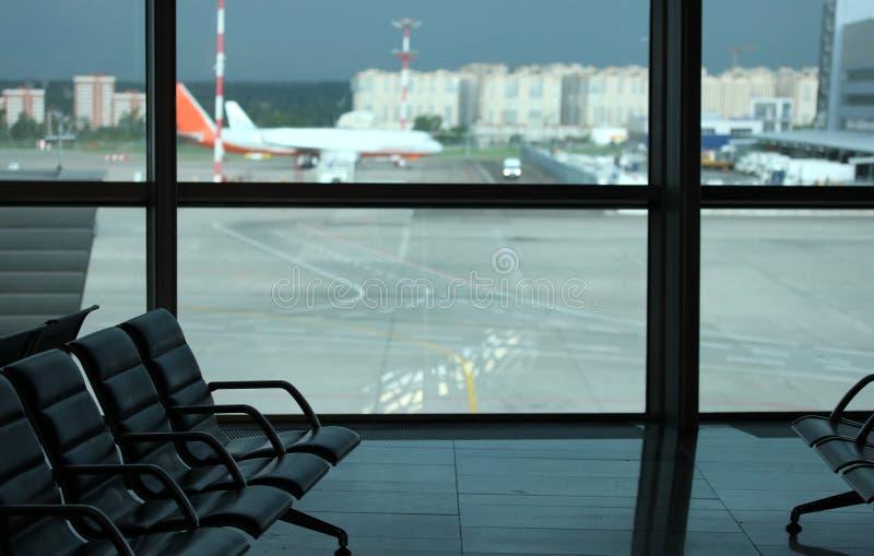 Assenta o close-up no aeroporto na sala de espera para a partida No fundo uma janela e uma pista de decolagem com aviões fotografia de stock