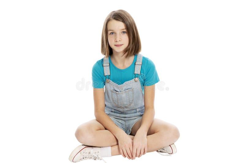 Assento adolescente bonito da menina Isolado em um fundo branco imagem de stock