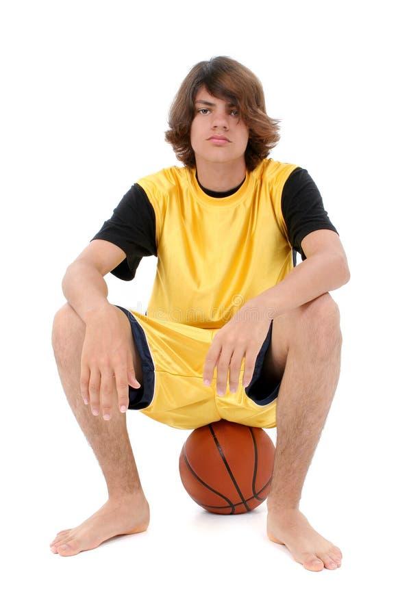 Assento adolescente do menino na esfera da cesta sobre o branco fotos de stock royalty free