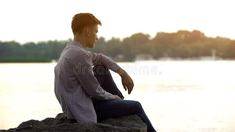 Assento adolescente masculino melancólico apenas na pedra perto do rio e pensamento sobre a vida fotografia de stock