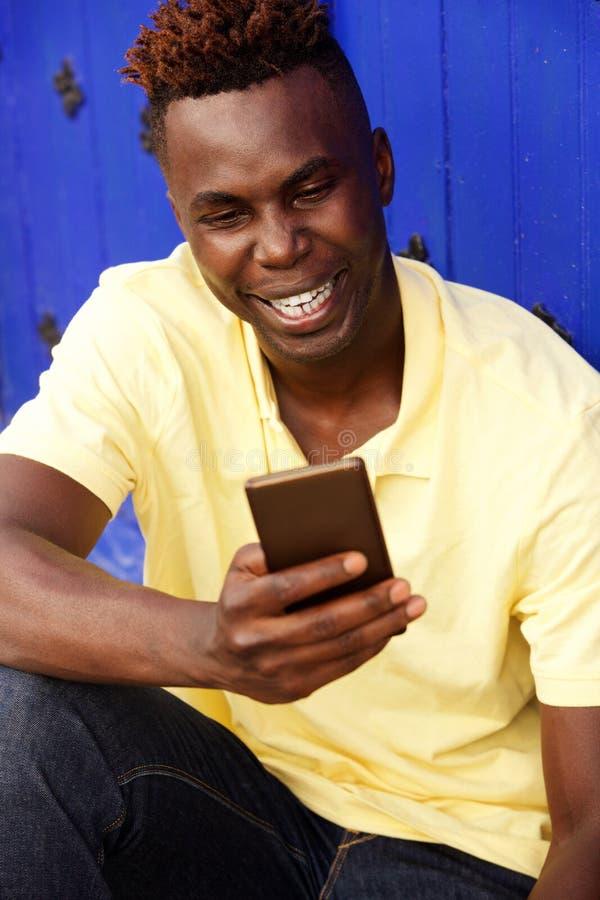 Assento afro-americano novo alegre do homem exterior e utilização do telefone celular foto de stock