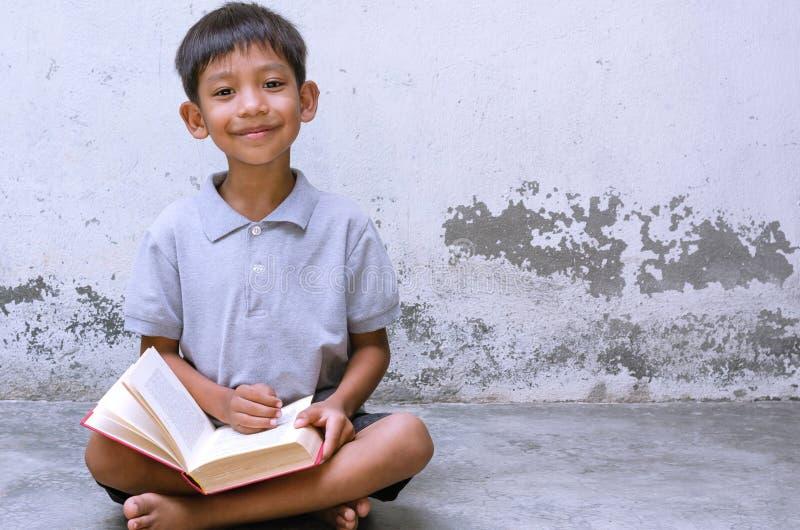 Assento asiático da criança e para sentir feliz com um livro imagens de stock royalty free