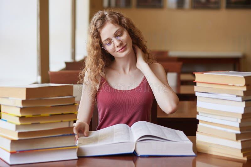 Assento bem-educado curioso na mesa na biblioteca, preparando-se para o exame, tocando em seu pescoço com a uma mão, fazendo a ma imagens de stock royalty free