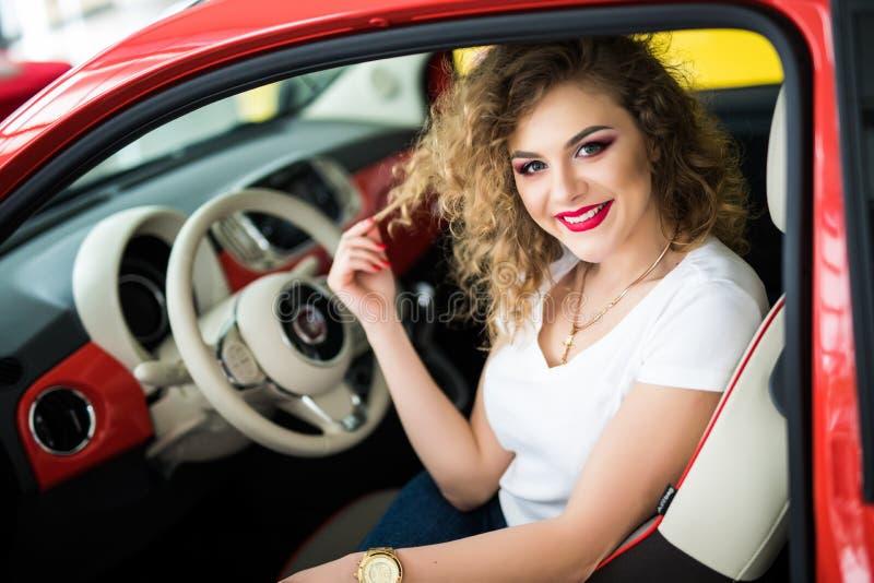 Assento bonito da jovem mulher em seu carro novo imagens de stock