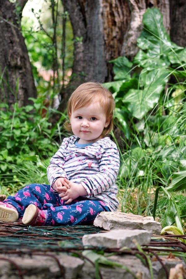Assento bonito do bebê, sorrindo e levantando, retrato A menina bonito pequena é brincalhão no jardim A criança está jogando fora imagens de stock