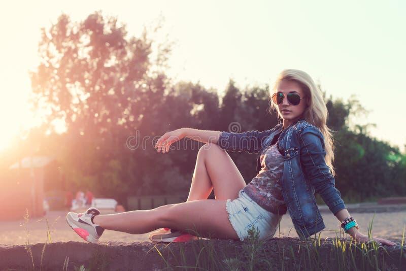 Assento bonito dos óculos de sol da jovem mulher da forma imagens de stock royalty free
