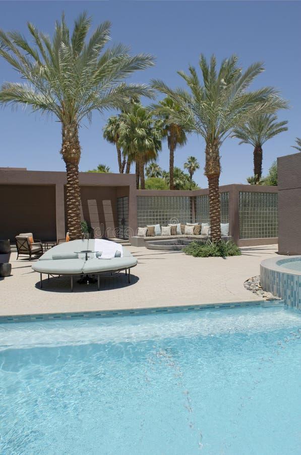 Assento com as palmeiras na piscina da casa fotografia de stock