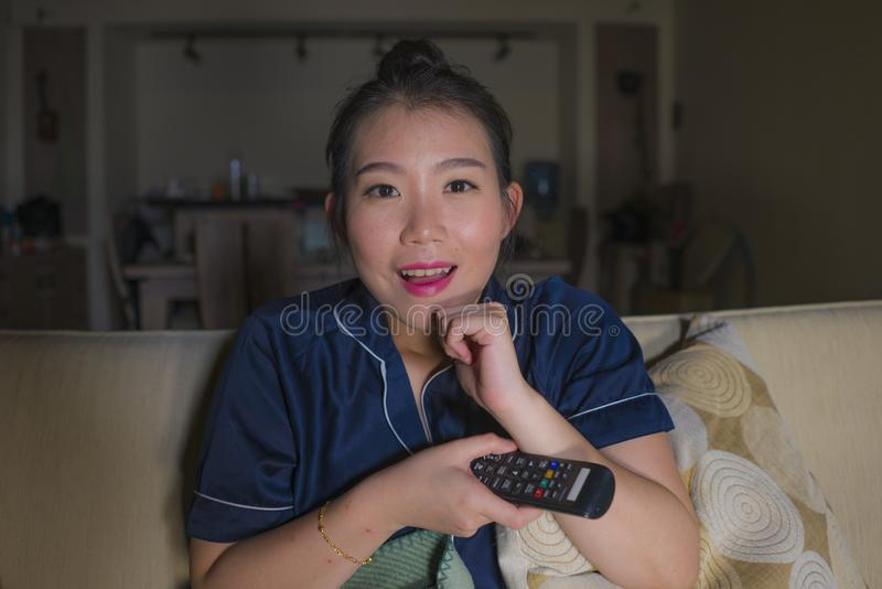 Assento coreano asiático feliz e relaxado bonito novo da sala de visitas da mulher em casa acolhedor no episódio de observação do foto de stock royalty free
