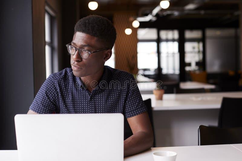 Assento criativo masculino preto milenar em um escritório usando o portátil, olhando fora da janela, fim acima imagens de stock