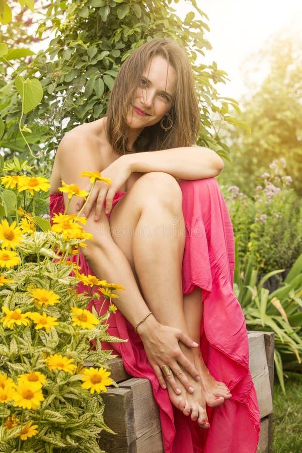 Assento da jovem mulher cercado por flores imagem de stock
