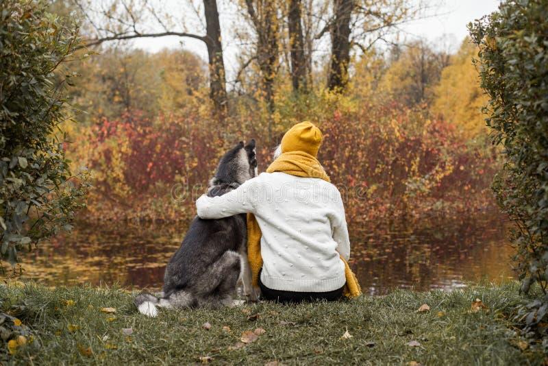 assento da mulher e do cão e divertimento roncos ter junto fotografia de stock