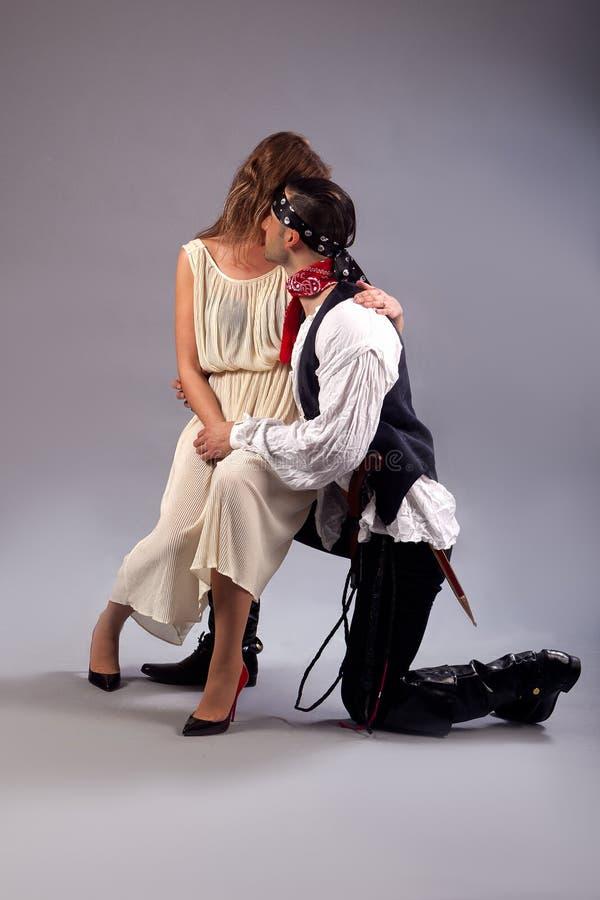 Assento da mulher tímido no pirata do homem do joelho fotografia de stock
