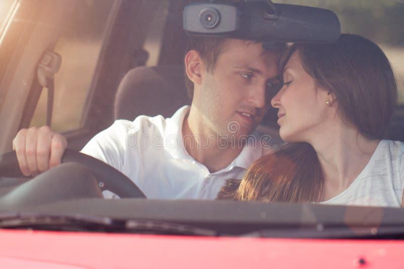Assento de beijo romântico no carro, horas de verão dos pares do sorriso dos jovens foto de stock royalty free