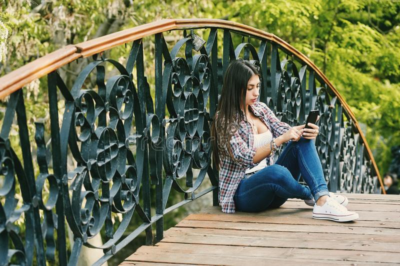 Assento de descanso da jovem mulher em uma ponte de madeira imagem de stock