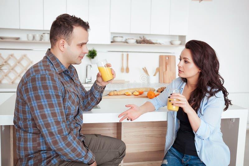 Assento de fala dos pares felizes na cozinha no café da manhã imagens de stock