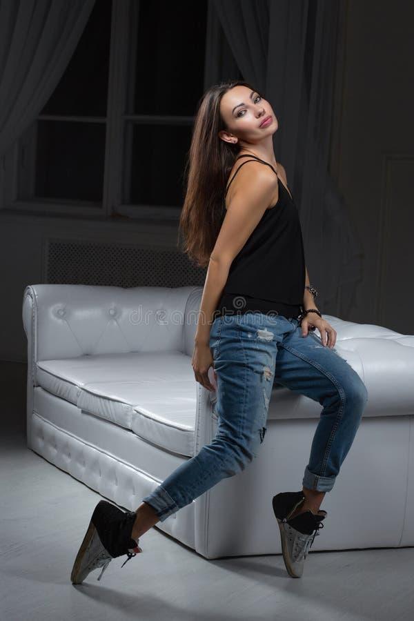 Assento de levantamento moreno atrativo em um sofá fotografia de stock royalty free