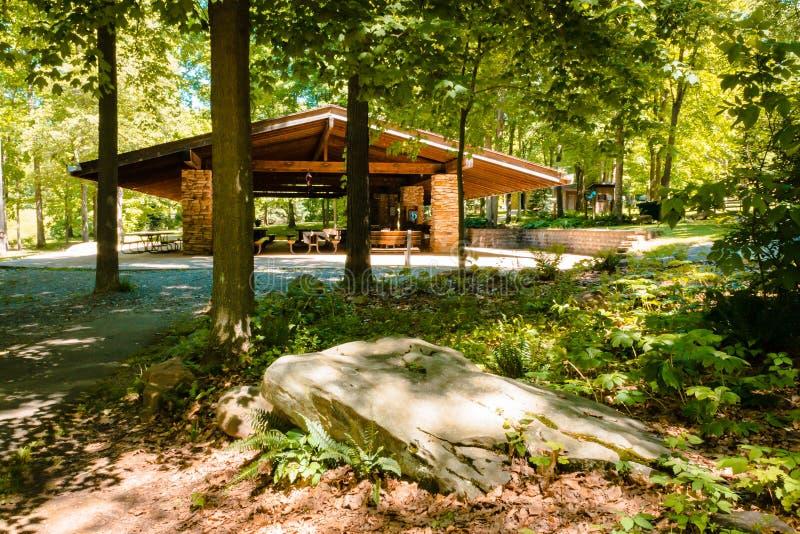 Assento de pedra na frente de um pavilhão do piquenique no parque Spruce azul durante o verão fotografia de stock