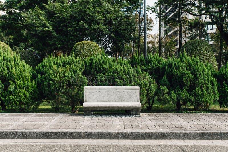 Assento de pedra no parque com os pinheiros no fundo na área do Dr. nacional Sun Yat-sen Memorial Hall em Taipei, Taiwan imagens de stock royalty free