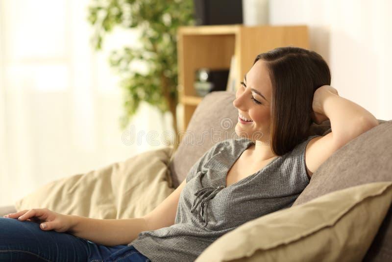 Assento de pensamento da menina relaxado em um sofá imagens de stock